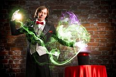 Magician causes the magic out of the hat. Wizard casts a spell over his hat from the hat off smoke, colored lights and magic Royalty Free Stock Images