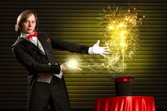 Magician causes the magic out of the hat. Wizard casts a spell over his hat from the hat off smoke, colored lights and magic Royalty Free Stock Photo