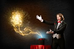 Magician causes the magic out of the hat. Wizard casts a spell over his hat from the hat off smoke, colored lights and magic Stock Photo