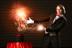 Magician causes the magic out of the hat. Wizard casts a spell over his hat from the hat off smoke, colored lights and magic Stock Photography