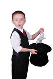 Magician Child. Child dressed as a magician pulling a rabbit from his hat isolated over a white background royalty free stock photography