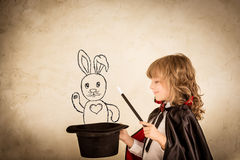 Magician. Child magician holding a top hat with drawn rabbit against grunge background. Focus on the hat Royalty Free Stock Images