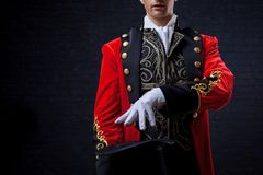 Magician. Close-up of hand in gloves The guy in the red camisole and the cylinder. Bright tailcoat, suit stock image