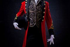 Magician. Close-up of hand in gloves The guy in the red camisole and the cylinder. Bright tailcoat, suit stock photo