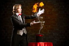 Magician. Conjures a stream of fire out of the hat Stock Photo