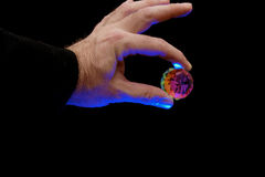 Magician with crystal. Magician holding faceted crystal, theatrical blue lighting illuminates the hand against a black background Stock Image