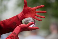Magician demonstrates trick with glass sphere Royalty Free Stock Photo