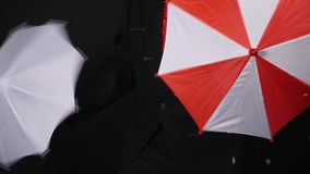 Magician doing tricks with umbrellas on black background.  stock footage