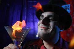 Magician with flaming martini. Glass Stock Photos