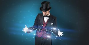 Magician with geometrical connection on his hand. Magician with blue background and geometrical connection between two hands Royalty Free Stock Image