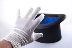 Magician hand in white silky glove reaches for classic top hat Royalty Free Stock Photography