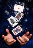 Magician hands with cards. Hands of a magician with cards floating over a space background Royalty Free Stock Photo
