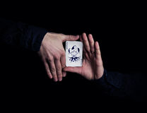 Magician hands. Close up of hands holding joker playing card. Magician showing his trick with cards on black background Royalty Free Stock Photography