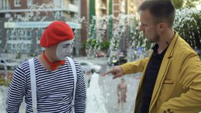 Magician has fun with funny mime. Two street actors have fun together and show each other their professional skills. People are standing on the urban square at stock video footage