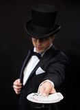 Magician in hat showing trick with playing cards Stock Photography