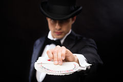 Magician in hat showing trick with playing cards Royalty Free Stock Image