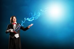 Magician. Holding a cylinder where the magic fly Royalty Free Stock Image