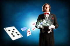 Magician. Holding a cylinder, from which fly out of playing cards Royalty Free Stock Photography
