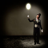 Magician holding a glowing balloon. Magician in top hat and tie, holding a glowing baloon, and staring at him Royalty Free Stock Image
