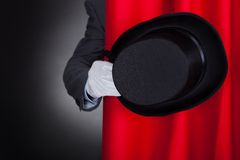 Magician holding hat behind stage curtain Royalty Free Stock Images
