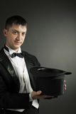 Magician holding magic hat Royalty Free Stock Image