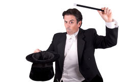 Magician holding a magic wand. And a hat isolated over white background Stock Photos