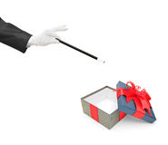 Magician holding a magic wand over a gift Royalty Free Stock Images