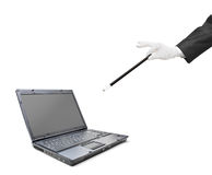 A magician holding a magic wand over a laptop Royalty Free Stock Photography
