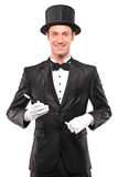 A magician holding a magic wand and posing Stock Image