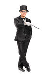 Magician holding a magic wand posing Royalty Free Stock Photography