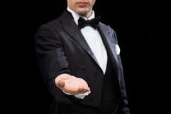 Magician holding something on palm of his hand. Magic, performance, circus, show and advertisement concept - magician holding something on palm of his hand royalty free stock photography
