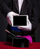Magician holding tablet pc over his accessories for work Royalty Free Stock Photos
