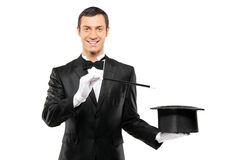 A magician holding a top hat and magic wand. A magician in a black suit holding an empty top hat and magic wand isolated on white background Stock Photo
