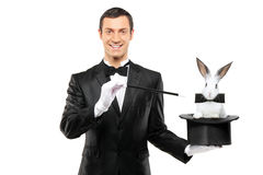 A magician holding a top hat with a rabbit in it. A magician in a black suit holding a top hat with a rabbit in it isolated on white background Stock Photos