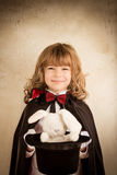 Magician holding a top hat with a toy rabbit Royalty Free Stock Photo