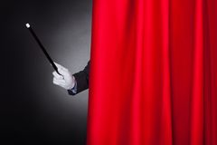 Magician holding wand behind stage curtain Stock Images