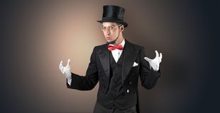 Magician holds something invisible. Handsome magician with no graph holds something invisible royalty free stock image