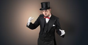 Magician holds something invisible. Handsome magician with no graph holds something invisible royalty free stock photo