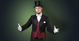 Magician holds something invisible. Handsome magician with no graph holds something invisible stock images