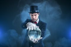 Magician or illusionist is fortune telling and predicting future from magical crystal ball.  Royalty Free Stock Images