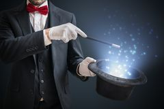 Magician or illusionist is showing magic trick. Blue stage light in background.  Royalty Free Stock Photography