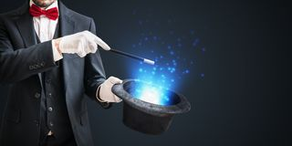 Magician or illusionist is showing magic trick with wand and hat on dark background royalty free stock photography