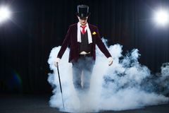 Magician, Juggler man, Funny person, Black magic, Illusion standing on the stage with a cane of beautiful light Stock Images