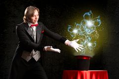 Magician. Makes passes at the cylinder, the cylinder produces magic Royalty Free Stock Photography
