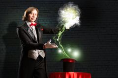 Magician. Makes passes at the cylinder, the cylinder produces magic Royalty Free Stock Photo