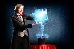 Magician. Makes passes at the cylinder, the cylinder produces magic Royalty Free Stock Photos