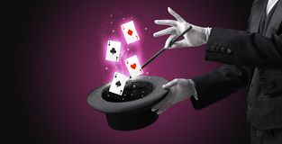 Magician making trick with wand and playing cards. Magician with white gloves conjuring playing cards from a cylinder with magic wand stock photos