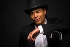 Magician man winking. Magic, performance, circus, show concepts. Magician man in top hat, leaning on cane, going to perform different tricks Stock Photos