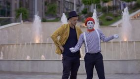 Magician and mime have fun standing at the background of illuminated fountains. Ilusionist and mime have fun standing near the illuminated fountains at the urban stock video