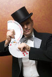 Magician performing with cards. Magician make performance with card deck Stock Photography